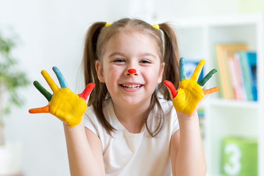 cute cheerful child with painted hands and face